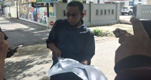 Defrianto Tanius memperlihatkan bukti-bukti usai melaporkan Kasat Pol PP Padang Alfiadi terkait dugaan pelanggaran netralitas ASN ke Bawaslu Sumbar.