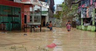 Anak anak asyik bermain di tengah permukiman warga yang sedang dilanda banjir.