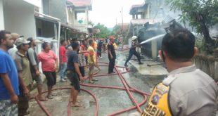 Petugas Damkar melakukan penyemprotan air ke rumah yang mengalami kebakaran, sementara warga di sekitar panik karena takut api makin menyebar